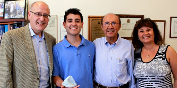 "Evan Goldstein (second from left) holds the tiny knitted cap he wore when he was born eight weeks prematurely at the JGH on Nov. 18, 1987, weighing 1,587 grams (3½ pounds). This past July, after receiving his Master's degree in Communications and Public Relations from Boston University, he visited Dr. Apostolos Papageorgiou (second from right), the JGH Chief of Pediatrics, with his parents, Lloyd and Judi. They thanked Dr. Papageorgiou for Evan's care by making a donation to The Auxiliary's Tiny Miracle Fund—co-chaired by Hela Boro, Robyn Brojde, Roz Rinzler and Lucy Wolkove—to help purchase 20 incubators for the Neonatal Intensive Care Unit. ""We've been talking for a while about helping the hospital,"" said Mr. Goldstein, ""and when we heard about the Tiny Miracle Fund, we knew this was the time to do what we could."" During the visit, Mrs. Goldstein also showed Dr. Papageorgiou an album of Evan's baby pictures, as well as the identification bracelet he wore in the hospital."