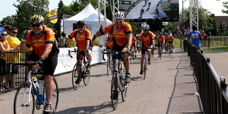 Phil Anzarut (centre) gives a proud thumbs-up as he and members of his Bikus Urachus team cross the finish line in the 2015 Enbridge Ride to Conquer Cancer.