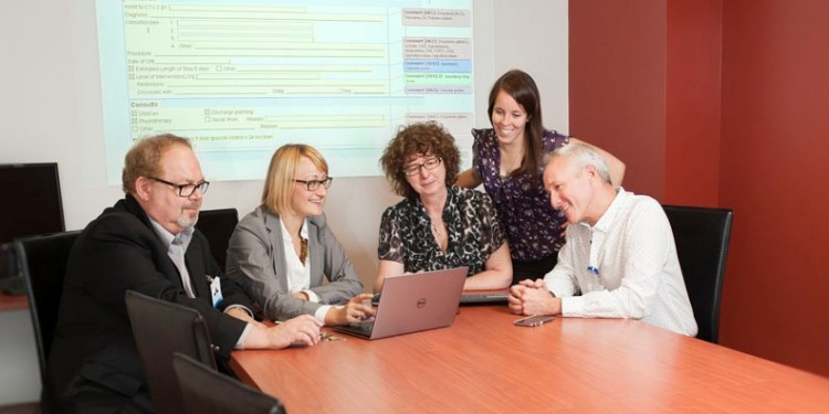 The team heading the implementation of the Patient Order Sets consists (from left) Bob Lapointe (IT Lead), Gosia Radaczynska (representative, Think Research), Dr. Elizabeth MacNamara (Medical Lead), Geneviève Beaudoin (Clinical Lead) and Serge Cloutier (Nursing Lead). Projected on the screen behind them is a sample Patient Order Set.