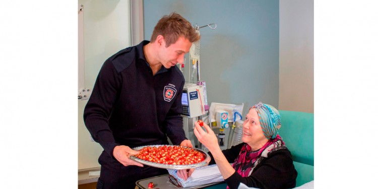 In the Segal Cancer Centre, Brigitte Huhn accepts a chocolate and Christmas greetings from Marc-André Geoffrion, an instructor at the Firefighters' Academy.