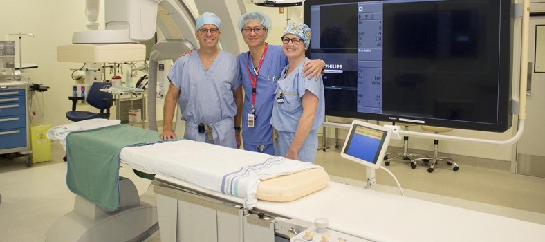 From left: Dr. Daniel Obrand (Chief of Vascular Surgery), Robert Woo (X-ray Technologist) and Karen Williams (Nurse and Team Leader in Vascular Surgery) in the hybrid surgical suite. At certain points during the surgery, the patient on the operating table (foreground) is x-rayed by the C-arm (far left), which sends images in real time to the large screen (far right).