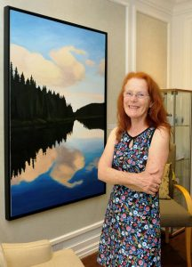 Nycol Beaulieu with a painting of hers that she donated to the Hope & Cope Cancer Wellness Centre.