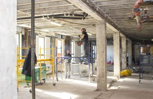 Workers inspect electrical wiring and pipes in the ceiling during demolition on the third floor of Pavilion B.
