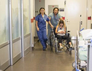 As the simulation begins, Demitra Horotan (left), a Nurse in the Emergency Department, leads the way to the Resuscitation Unit in Emergency.