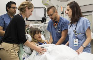 As the simulated labour begins, Respiratory Therapist Michael Ramadeen (left) is among those providing care to the pregnant patient, who is in considerable distress.