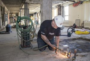 A member of the demolition team removes an old piece of pipe from the floor of Pavilion B, where the new Psychiatry In-Patient Care Unit will be built.