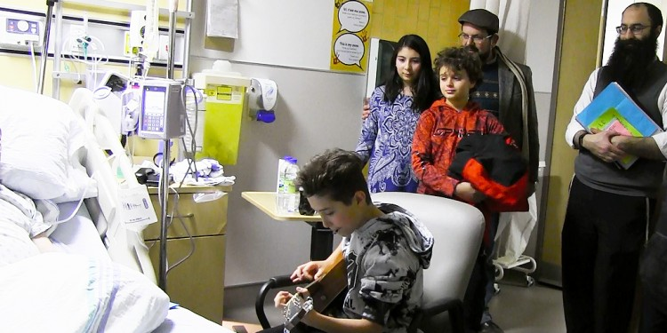 As Zane Burko plays guitar for an appreciative patient, Rabbi Barak Nissim Hetsroni (right) watches the JGH event, which he organized. Accompanying him from the Shaare Zion Congregation are volunteers (from left) Tamar Durazo-Hernández, Logan Winkler, and Tamar's father, Julián Durazo-Hernández.