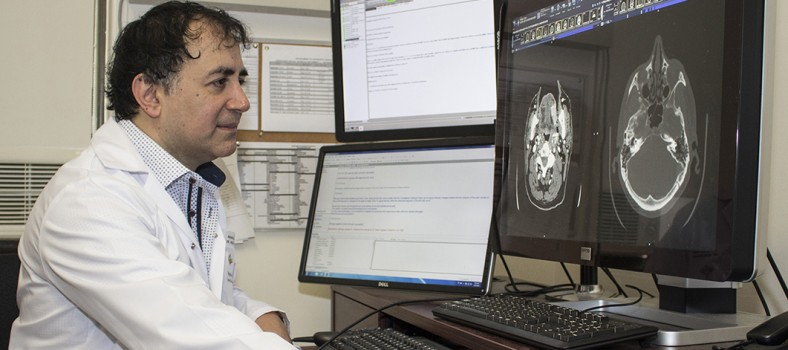 Dr. Reza Forghani examines the CAT scan of a patient's neck.