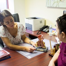 Dr. Polymnia Galiatsatos, a JGH Gastroenterologist, uses a model to explain to a patient how the digestive tract works.