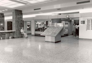 The lobby in the 1990s, with the main doors behind the photographer. At the centre is a directory of hospital offices and clinics, and behind it is The Auxiliary's flower shop. Today the main security desk has replaced The Auxiliary's book table (at left) and the passageway to Pavilion K begins where people are waiting for an elevator (at right).