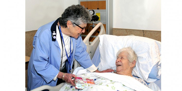 Jeannette Singerman, a volunteer in Palliative Care, shows a package of rose-shaped soaps to patient Leah Pasechnick, who chose to present them as a gift to a loved one.