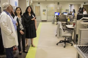In the green pod of the Emergency Department, Dr. Marc Afilalo explains to Danielle McCann how the work area is designed, with the central area reserved for healthcare staff, and patients' rooms on the perimeter.