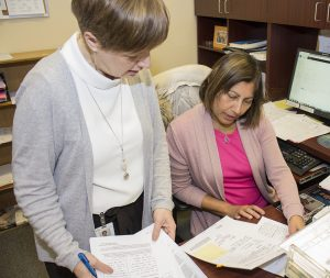 Nurse Clinician Stephanie Preston (left) confers with Administrative Officer Leila Fernandes to determine which patients need to be seen most urgently, as a follow-up to their treatment in the Emergency Department.