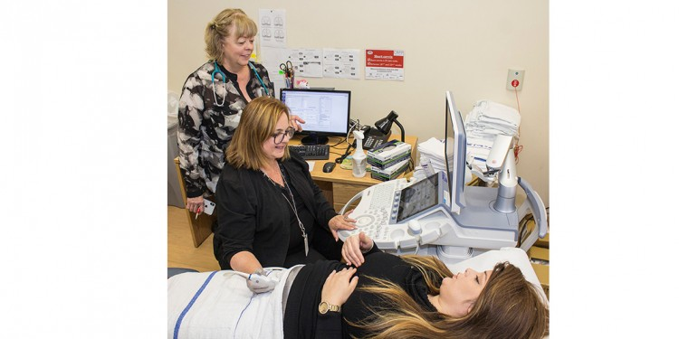 Mazit Ifergan undergoes an obstetrical ultrasound scan by Linda Larin (seated), a Specialized Ultrasound Technician, in consultation with Dr. Louise Miner.