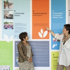 Arlene Greenberg and Linda Lei review the large commemorative poster that lists many of the JGH's most recent achievements.