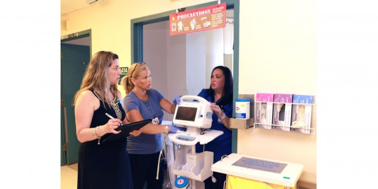 Proper disinfection of a blood-pressure machine is discussed by (from left) Silvana Perna, Coordinator of Infection Prevention and Control, nurse Debra Hyland, and Luisa Neri of Enviro Services. To minimize the spread of infectious microorganisms, a sign of precautionary instructions hangs over the door, clean gloves and disinfectant wipes are on the wall to the right of the door, and clean gowns are available in the receptacle to the right of the door.