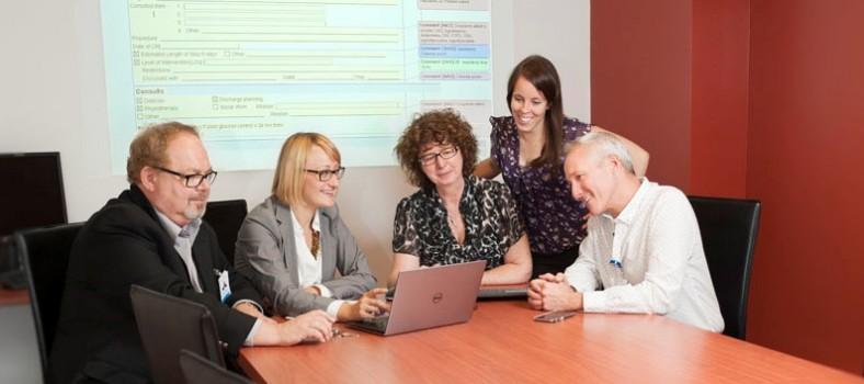 Le groupe ayant pour mandat de guider la mise en œuvre du projet des ordonnances électroniques est formé (de gauche à droite) de Bob Lapointe (TI), Gosia Radaczynska (représentante, Think Research), la Dre Elizabeth MacNamara (médicale), Geneviève Beaudoin (clinique) et Serge Cloutier (soins infirmiers). En arrière-plan, un exemple d'une ordonnance électronique est projetée sur l'écran.