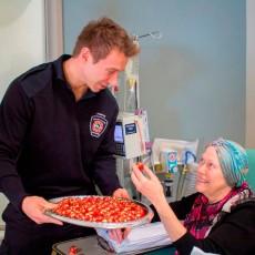 Au Centre du cancer Segal, Marc-André Geoffrion, instructeur à l'Académie des pompiers, donne du chocolat à Brigitte Huhn en lui adressant ses meilleurs vœux pour Noël.