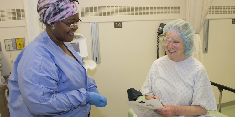In the recovery room of the Academic Cataract Centre, Claire Lenet receives instructions from Nursing Assistant Francine Mwimbi about the post-surgical care of her right eye.