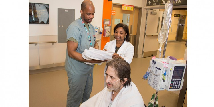 Before Michael Lee is taken by wheelchair for a test, the safety and adequacy of his oxygen supply are reviewed and confirmed by Yves-Alex Dejean, a Transport Attendant, and by Vanessa Roberts, an Education Consultant in Respiratory Therapy, who helped develop the new policy on transporting patients on oxygen.