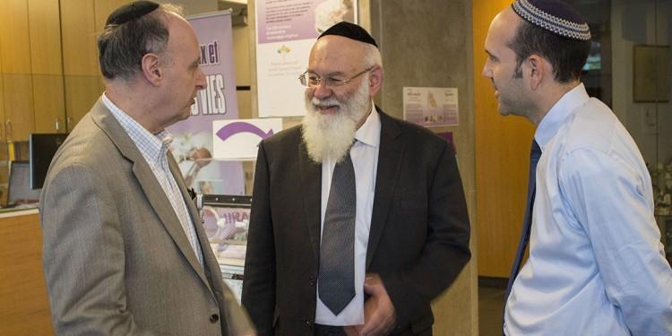 Le rabbin Avraham Steinberg (au centre) est accueilli à l'Hôpital général juif par le Dr Lawrence Rosenberg (à gauche), président-directeur général du CIUSSS du Centre-Ouest-de-l'Île-de-Montréal, et par le Dr Michael Bouhadana, organisateur du symposium.