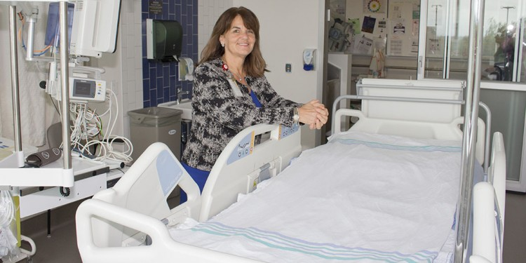 Jacki Raboy Thaw stands beside the type of therapeutic bed that was transported from the JGH to Mount Sinai Hospital to fulfill the Magic Moment of a Palliative Care patient.