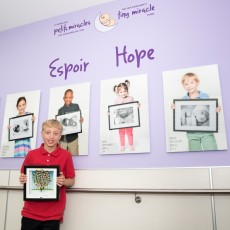 At the Wall of Hope in the Neonatal Intensive Care Unit, Josh Samuels holds the plaque that he received from the JGH Auxiliary for raising $4,200 for the Tiny Miracle Fund. The donation, which commemorated his bar mitzvah, was raised through a basketball clinic and tournament at his school, Hebrew Academy.