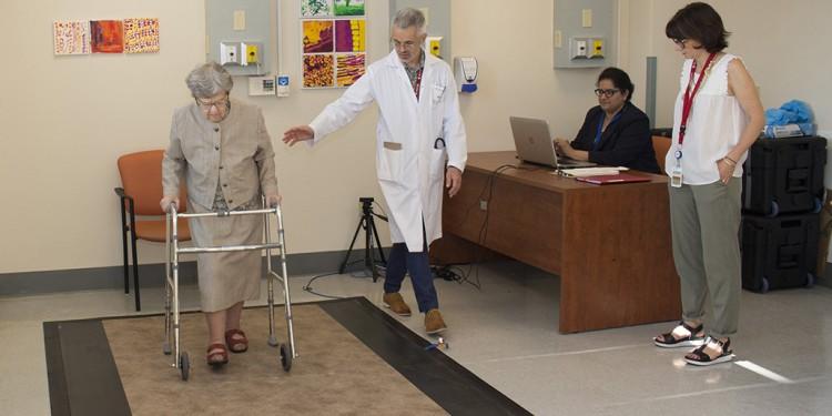 À la Clinique de la mobilité de l'HGJ, la démarche de Jacqueline Deland, qui est âgée de 98 ans, est évaluée pendant qu'elle marche sur un tapis spécial, sensible à la pression, qui est relié à un ordinateur. Le Dr Olivier Beauchet (au centre) supervise le test au cours duquel l'information numérique est recueillie par Harmehr Sekhon (assise), une adjointe en recherche clinique. La gérontologue Samantha Remondière, participe également à l'examen.