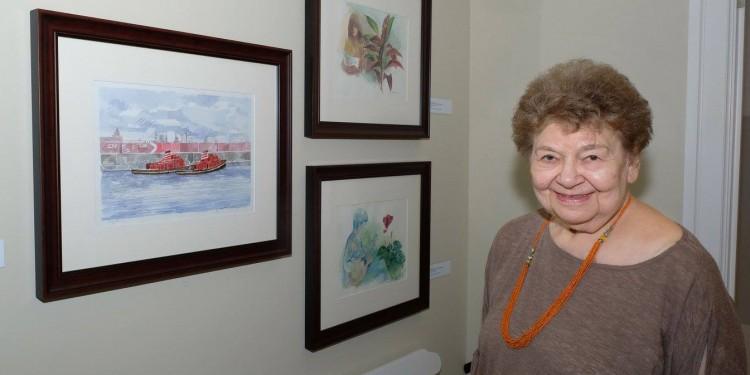Rita Briansky, au Centre de bien-être pour le cancer de l'Espoir, c'est la vie, avec un tableau (à gauche) de son défun mari, Joseph Prezament, et deux de ses propres aquarelles.