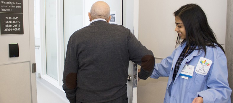 Rabbia Akhtar-Tariq, une étudiante bénévole à l'Unité des soins intensifs médicaux-chirurgicaux, aide un membre de la famille d'un patient à entrer dans l'Unité.