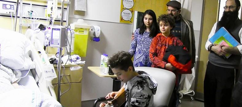 Tandis que Jeremy Gordon joue de la guitare pour un patient reconnaissant, le rabbin Barak Nissim Hetsroni (à droite) observe cette activité qu'il a organisée pour l'HGJ. Les bénévoles qui l'accompagnent de la congrégation Shaare Zion sont (de la gauche) Tamar Durazo-Hernández, Logan Winkler, et le père de Tamar, Julián Durazo-Hernández.