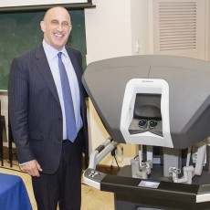 Michael Flinker (left) and Jean-Luc Trahan, prostate cancer survivors, with the type of console used in the robotic surgery that they believe saved their lives.