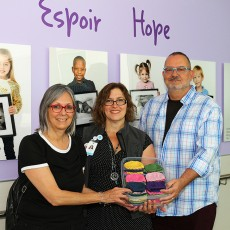 The Knitting Bees Club, based at CLSC Benny Farm, recently donated nearly 100 hats to the JGH Neonatal Intensive Care Unit (NICU). From left in the NICU corridor are Johanne Dugas, Lyne Charbonneau and André Charbonneau.