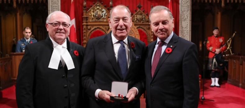 Le 31 octobre, au Sénat à Ottawa, Bernard Stotland (au centre) reçoit une médaille du 150e anniversaire du Sénat du Canada, des mains du Président du Sénat, l'honorable George J. Furey (à gauche), et du sénateur Serge Joyal.
