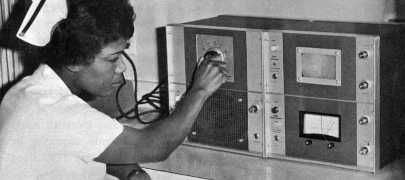 En 1967, l'infirmière Vashti McClean tourne le commutateur du nouveau système de surveillance de la fréquence cardiaque fœtale de l'HGJ. Elle écoute le cœur d'un bébé à naître grâce à un amplificateur (coin inférieur gauche) et elle en observe les battements sur un oscilloscope (coin supérieur droit).