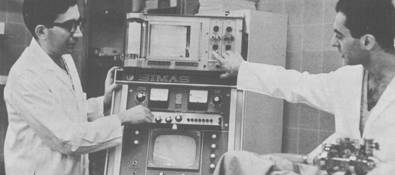 Technician José Ruiz (left) and Dr. Francisco Merino, a Canadian Research Fellow, demonstrate the computerized heart-assist pump that was used at the JGH in 1968.