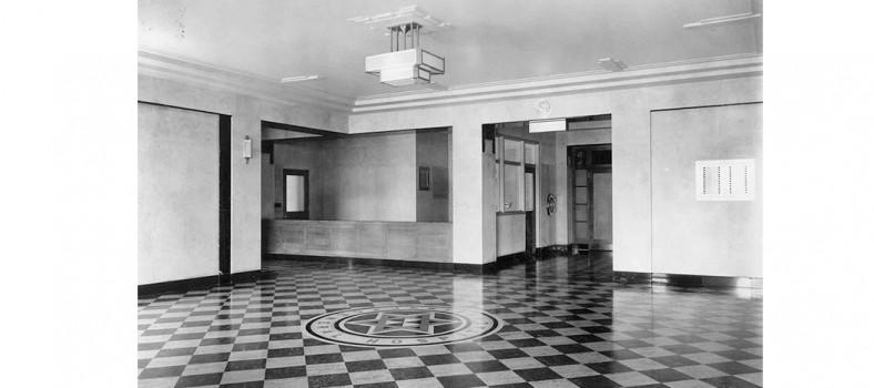 Le hall d'entrée principal original de l'HGJ, comportant une étoile de David et le nom de l'Hôpital gravés dans les carreaux du plancher. Le bureau d'information est au centre de la photo, et la porte est derrière le photographe.
