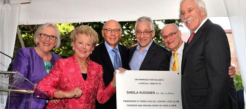 En septembre 2014, la fondatrice de l'organisme L'espoir, c'est la vie, Sheila Kussner (deuxième à partir de la gauche), a reçu une plaque honorifique qui lui a été remise par (de gauche à droite) Suzanne O'Brien, directrice générale de L'espoir, c'est la vie, Howard Dermer, président de la Fondation de l'HGJ, le Dr Gérald Batist, chef du Service d'oncologie de l'HGJ et directeur du Centre du cancer Segal, Myer Bick, président-directeur général de la Fondation de l'HGJ et Allen Rubin, président de l'HGJ.