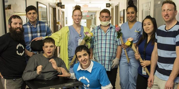 Les visiteurs du Cercle de l'amitié font naître des sourires sur les visages des patients du pavillon K et leur apportent des fleurs. Debout, de gauche à droite : rabbin Leibele Rodal (adjoint du directeur général du Cercle de l'amitié), Noam Schwartz, Samantha McCullough (infirmière), Shaun Benharroch, Vanessa Vincent (infirmière), Felicia Hua (infirmière) et Shaun Menard. Assis : Richard Stern (à gauche) et Chaim Wenger.