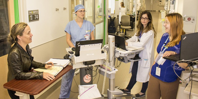 At a team meeting to discuss medication in the Cardiovascular Intensive Care Unit, Nurse Kamylle Martin (right) works at her medication cart, while conferring with (from right) Pharmacist Helen Mantzanis and medical student Ellen Dunbar-Lavoie (each using a work-station on wheels), and Dr. Judith Therrien.