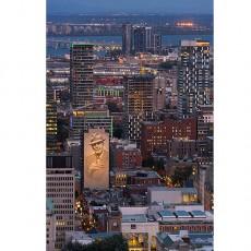 Dans sa photo gagnante du concours « Une pose de bonheur », Vidette Uon, infirmière à Info-Santé, a saisi la silhouette lumineuse de la ville de Montréal lors d'un coucher du soleil du mois d'août. L'énorme murale Tower of Songs, fresque peinte sur le côté d'un édifice en hommage à l'auteur-compositeur Leonard Cohen, domine la photo.