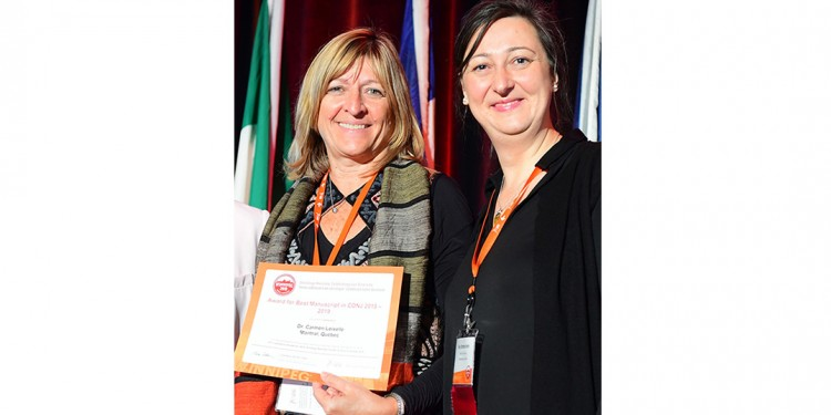 Dr. Carmen Loiselle (left) receives an award from the Canadian Association of Nurses in Oncology, presented by her former doctoral student, Fay Stroshchein.