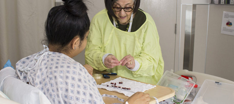 Rhoda Smith, a volunteer in The Auxiliary's Ante Partum Program, shows Adriana Rosales how to use wooden beads to make a bracelet. This helps Ms. Rosales to pass the time creatively during her lengthy hospitalization, while her high-risk pregnancy is monitored.