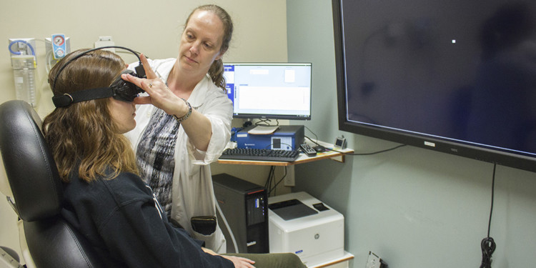 Audiologist Voula Tsagaroulis adjusts the goggles that help measure a visual reflex related to the patient's ability to keep her balance. In addition to performing hearing tests, audiologists play a broader role in assessing various aspects of balance and dizziness—in this case, by having the patient's eyes track the movement of the small white square on the screen.
