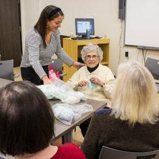 Bénévole de longue date à l'Institut de psychiatrie communautaire et familiale, Noami Weiss, 96 ans (au centre) — la plus vieille bénévole de l'HGJ — met à profit ses talents pour enseigner le tricot aux membres du groupe, animé par l'ergothérapeute Allana Goodman (debout).