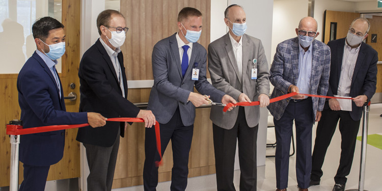 With faces covered to prevent the spread of COVID-19, leaders cut the ribbon to officially open the JGH's Carole and Andrew Harper Psychiatry Inpatient Unit. From left: Tung Tran, Director of the Mental Health and Addition Program of CIUSSS West-Central Montreal; Larry Sidel, Executive Vice-President of the JGH Foundation; Dr. Karl Looper, JGH Chief of Psychiatry; Dr. Lawrence Rosenberg, President and CEO of the CIUSSS; Edward Wiltzer, Past Chairman of the Board of the JGH Foundation; and Bram Freedman, President and CEO of the Foundation.