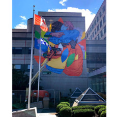 In late August, the finishing touches were placed on the painted mural that covers much of the eastern wall of Pavilion G, facing the hospital's main entrance. The mural depicts a grateful patient and a healthcare worker, who embrace while wearing protective clothing. Swirling around them are large versions of the leaves that appear in the JGH logo. (Click on the photo to enlarge it.)