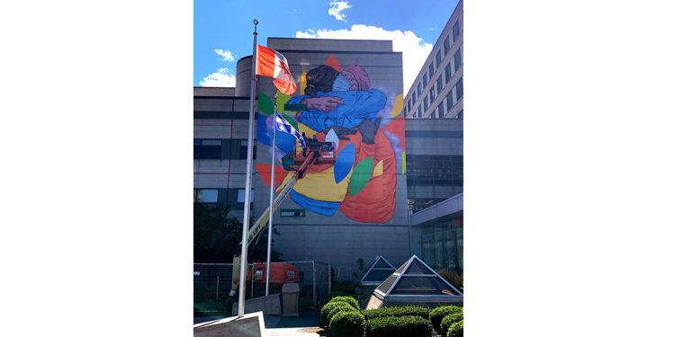 Fin août, les dernières touches ont été apportées à la fresque murale qui couvre une grande partie du mur est du pavillon G, devant l'entrée principale de l'Hôpital. La murale illustre un patient reconnaissant et un travailleur de la santé qui s'étreignent, tous deux vêtus d'équipement de protection individuelle. Des versions agrandies des feuilles illustrées dans le logo de l'HGJ tourbillonnent autour d'eux. (Cliquez sur la photo pour l'agrandir.)