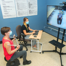 At the Constance-Lethbridge Rehabilitation Centre, Sacha Vincent-Toskin (left), an Occupational Therapist, and Michele Mercier, an Orthotic/Prosthetic Technician, connect to a long-term care centre. During this telehealth session, they work with a client (seen on-screen in a wheelchair) and with Occupational Therapist Patrice Lu to custom-design a wheelchair for the client.