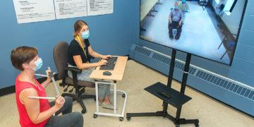 Au Centre de réadaptation Constance-Lethbridge, l'ergothérapeute Sacha Vincent-Toskin (à gauche), et la technicienne en orthèses/prothèses, Michèle Mercier, se connectent à un centre de soins de longue durée. Pendant cette séance de télésanté, elles regardent l'écran et collaborent avec un client (assis dans un fauteuil roulant) et avec l'ergothérapeute Patrice Lu pour dessiner un fauteuil roulant sur mesure.